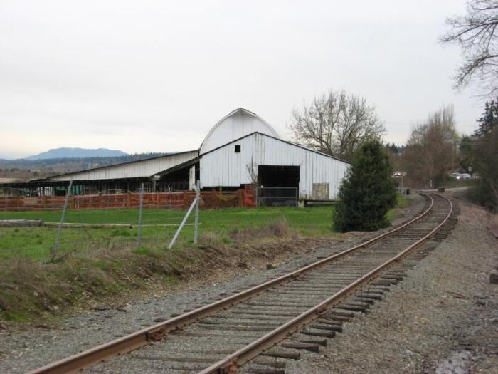The track passing by a white barn