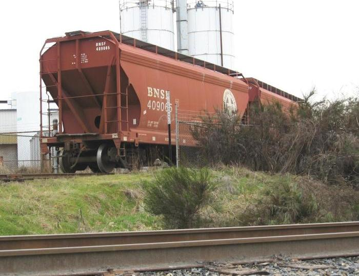 Two covered hopper cars sitting on embankment with silos in background