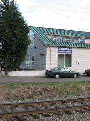 Modern white wooden building with track in foreground