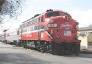 Red locomotive and several silver colored passenger cars