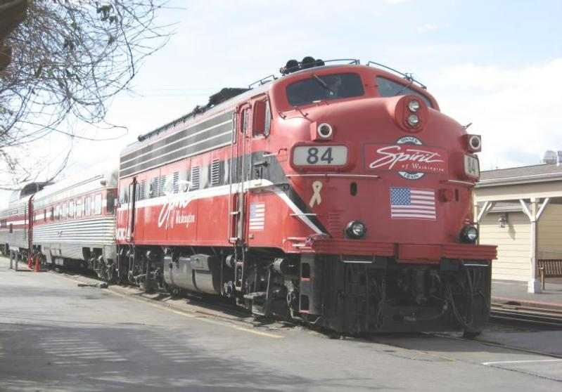 Red locomotive and several silver passenger cars of dinner train